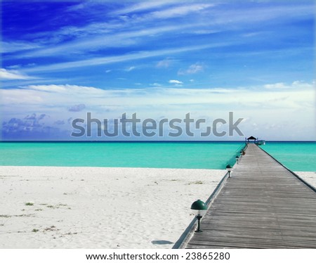 Wooden jetty on over the beautiful Maldivian beach with blue sky and clouds - stock photo