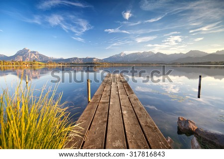 wooden Jetty on the lake named Hopfensee with the Alps and blue sky - stock photo