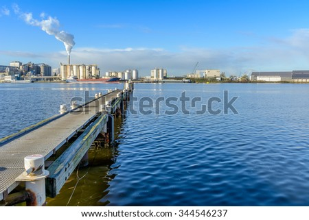 Wooden jetty with mooring bollards being used for merchant vessels.Nice Industry view at the background. - stock photo
