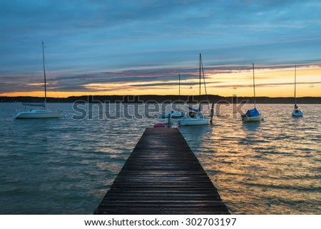 Wooden jetty with sailboats at Lake Ammersee, Buch, Bavaria, Germany - stock photo