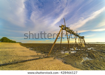 Wooden jetty with sunset background - stock photo