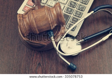 Wooden judge gavel, calculator and stethoscope on table - stock photo