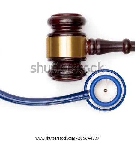 Wooden judge gavel, pills bottle and stethoscope on white backround - studio shot - stock photo