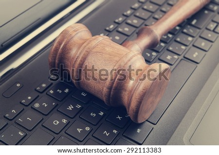 Wooden judge's gavel on a laptop computer, cyber law or crime concept - stock photo