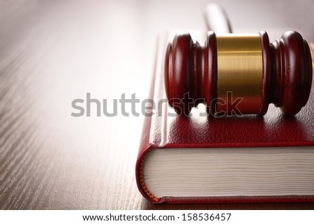 Wooden judges gavel lying on a law book in a courtroom for dispensing justice and sentencing crimes - stock photo