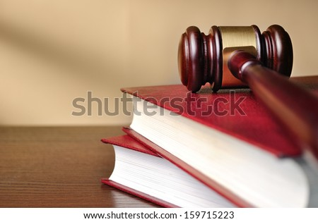 Wooden judges gavel with a brass band around the head resting on top of a closed red law book with shallow dof and copyspace - stock photo