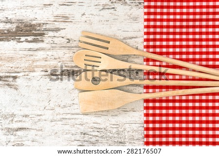 Wooden kitchen utensils and red tablecloth. Tools for food preparation - stock photo