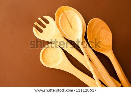 Wooden kitchen utensils lying on brown background. - stock photo