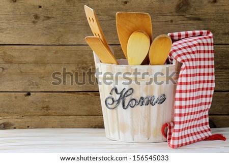 Wooden kitchen utensils on a wooden background - stock photo