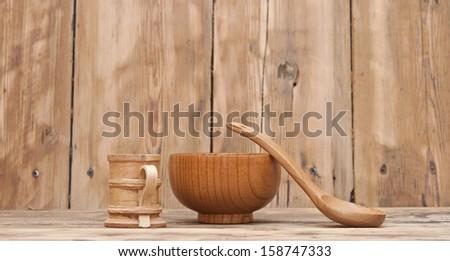 Wooden kitchen utensils on wooden table - stock photo