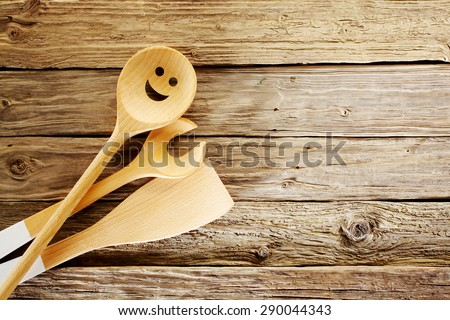 Wooden kitchen utensils with a spoon with a happy cutout face, and salad serves on aged textured wood arranged from the bottom left corner, with copyspace - stock photo