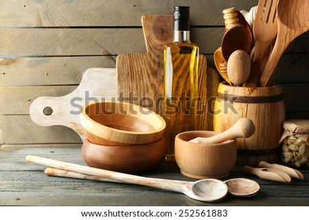 Wooden kitchen utensils with glass bottle of olive oil on wooden planks background - stock photo
