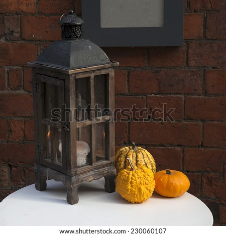 wooden lantern with pumpkins as a decoration of interior - stock photo