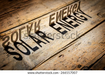 wooden letters on old aged wooden table build the shadow word solar energy, vintage style - stock photo