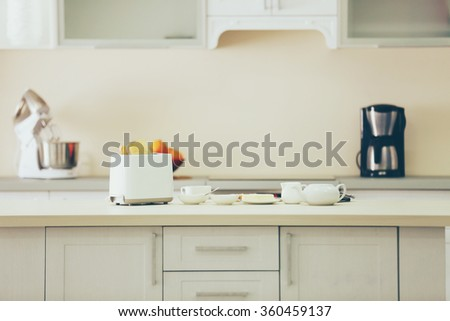 Wooden light table with toaster and dishes on a white kitchen background - stock photo