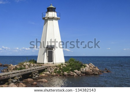 Wooden lighthouse by the lake - stock photo