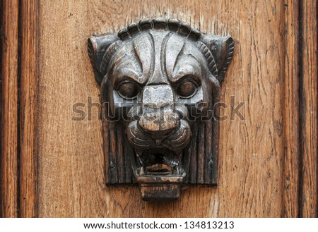 Wooden lion head relief - decorative element on ancient weathered door  in old part of Tallinn, Estonia - stock photo