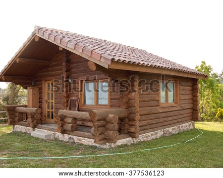 Wooden log house with lawn in the country - stock photo