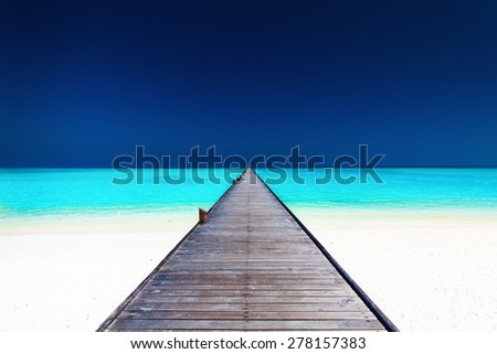 Wooden long jetty over lagoon with amazing clean azure water - stock photo
