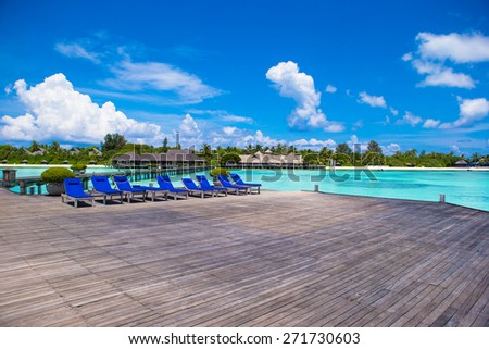 Wooden lounge chairs on on a wooden pier at Maldives - stock photo