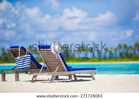 Wooden lounge chairs straw hat and bag on white tropical beach at Maldives - stock photo
