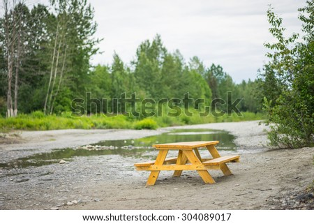 Wooden lunch table beside a calm stream in the woods and forest of Alaska. - stock photo