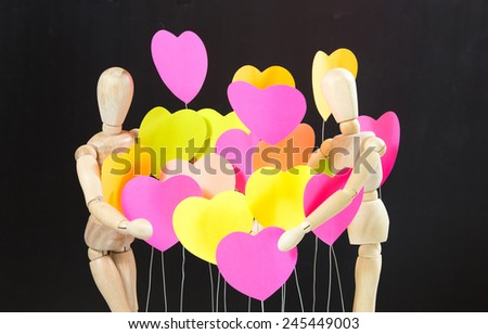 Wooden, male, female, are embracing the heart of all colors, background colors, Black - stock photo