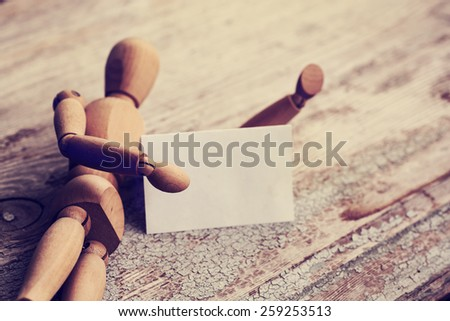 Wooden man model holding a business card as a copy space, laying on wooden background, Business background - stock photo