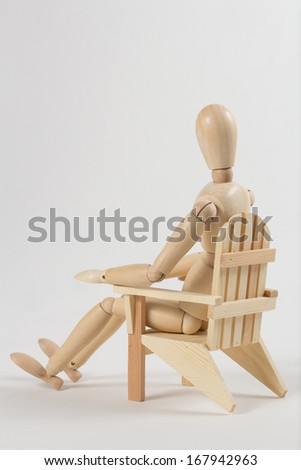 Wooden man sitting in a chair on white background  - stock photo