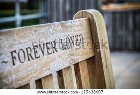 Wooden memorial bench with FOREVER LOVED carved into the back of it - stock photo