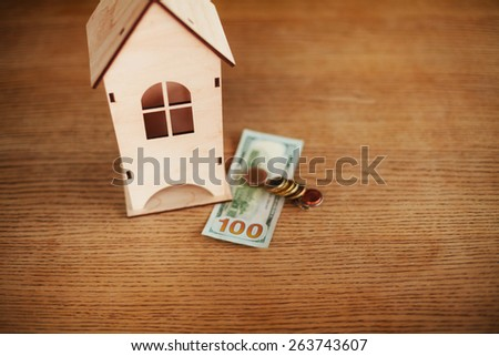 Wooden model of house with money on the table - stock photo