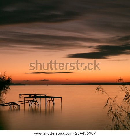 Wooden mole on the coast,morning by the Balaton lake  - stock photo