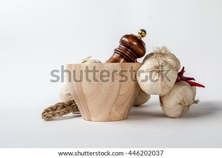Wooden mortar and pestle and garlic on white background - stock photo