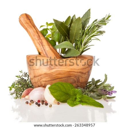 Wooden mortar filled with fresh herbs, isolated on white background - stock photo