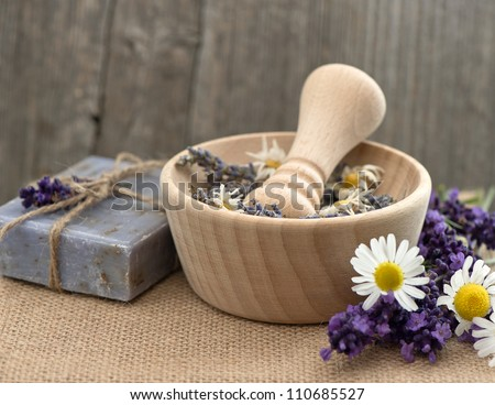wooden mortar with fresh lavender and chamomile flowers. selective focus - stock photo