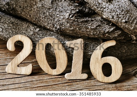 wooden numbers forming the number 2016, as the new year, with a pile of logs in the background, on a rustic wooden surface - stock photo