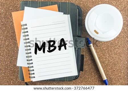 wooden office desk coffee and pen with word MBA on notebook - stock photo