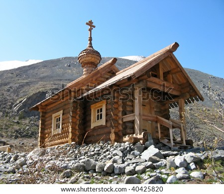 wooden Orthodox church in the mountains - stock photo