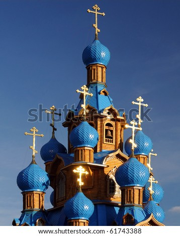 Wooden Orthodox church with blue domes and crosses shining in the sun - stock photo