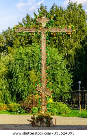 Wooden Orthodox cross carnations (Orthodox holiday) - stock photo