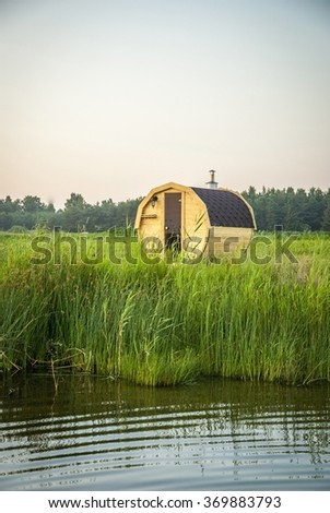 Wooden outdoor sauna by the lake in summer sunset - stock photo