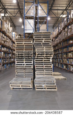 Wooden pallets and cardboard boxes stacked in distribution warehouse - stock photo