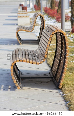 Wooden park bench in a sunny day - winter time - stock photo