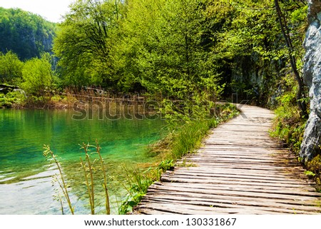 Wooden path near a forest lake in Plitvice Lakes National Park, Croatia - stock photo