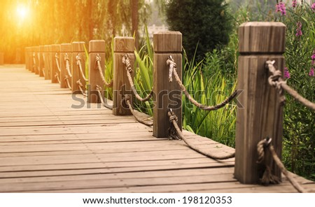 wooden path with railing in the park - stock photo