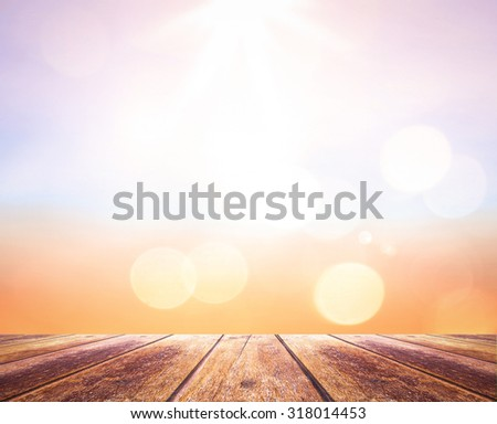 Wooden paving with abstract blurred textured background: yellow and green patterns. Blurred nature background. Sandy beach backdrop with turquoise water and bright sun light. Summer holidays concept. - stock photo