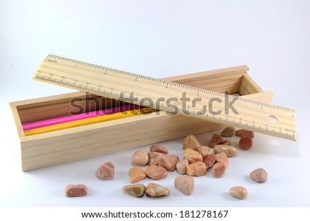 Wooden pencils box with ruler and little rock. - stock photo