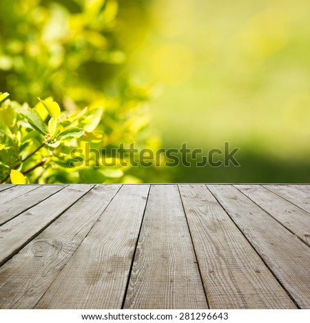 Wooden perspective floor with planks on blurred natural summer background, can use for display or montage your products template. Green forest with ray of light and bokeh. Copy space - stock photo