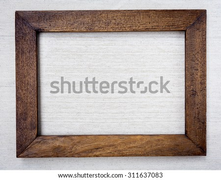 Wooden picture frame on canvas background - stock photo