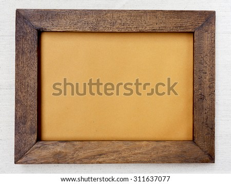 Wooden picture frame with brown paper background - stock photo